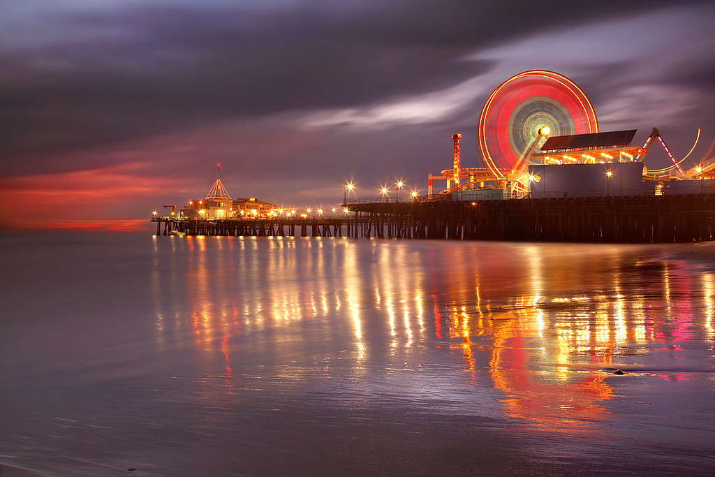 "This image was taken about 20 minutes after ""Santa Monica Spin1."" An extra long exposure and a little light still in the sky allowed the scene to become evenly lit. The wheel spun about 5 times during this exposure.   The spinning wheel turned out to be the most import factor to getting a good photograph.  Sometimes the wheel stopped, and the dynamic feel of the resulting image was lost.  Sometimes it would turn too quickly and become out of synch with the way the lights on the spokes worked, creating odd-looking effects.  So a lot of experimentation was required to get a smooth and dynamic look without distracting features.  Improvisation is often required to get the best photograph possible."