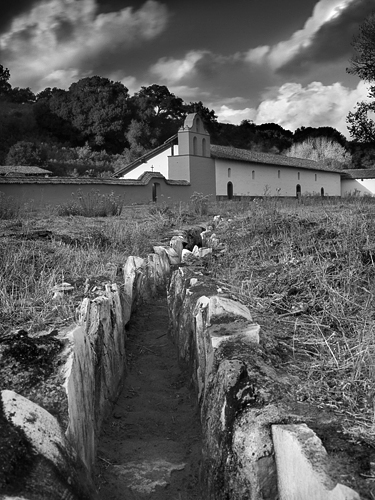 La Purisima water system with companario and chapel in background. Water was brought by pipe from natural springs to the springhouse, where it was filtered through sand. It then flowed through this aquaduct back to a main fountain near the mission for drinking and other uses.