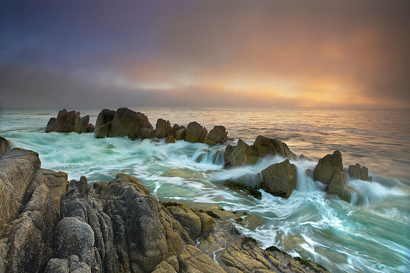 I have always liked the way the water moves through these rocks, so I waited for the atmosphere to be right before making this photograph.  Sometime I will wait for a year or more before conditions are right.  Finally, the fog lifted just enough to let in some color at first light at Lover's Point near Monterey and Pacific Grove.  The low angle of light also shows the color and texture of the rock at its best.  I liked the contrast of the sharp lines of surging water against the softness of the glowing fog.  I had to study the ebb and flow for quite some time in order to figure out how best to time the waves.  Rarely did all this action happen all at  once.