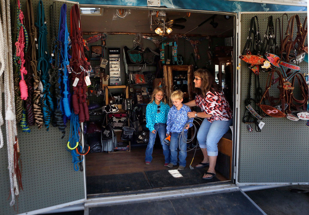 . Maci Cohn, 8, and her brother Max, 6, talk with Lynn Cordova inside Cordova\'s Steer Gear trailer during the California Rodeo Salinas at the rodeo grounds in Salinas on Thursday July 20, 2017. (David Royal/Herald Correspondent)