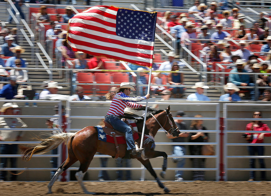 . A flag bearer runs in with an American flag at the start of the California Rodeo Salinas at the rodeo grounds in Salinas on Saturday July 22, 2017. (David Royal/Herald Correspondent)