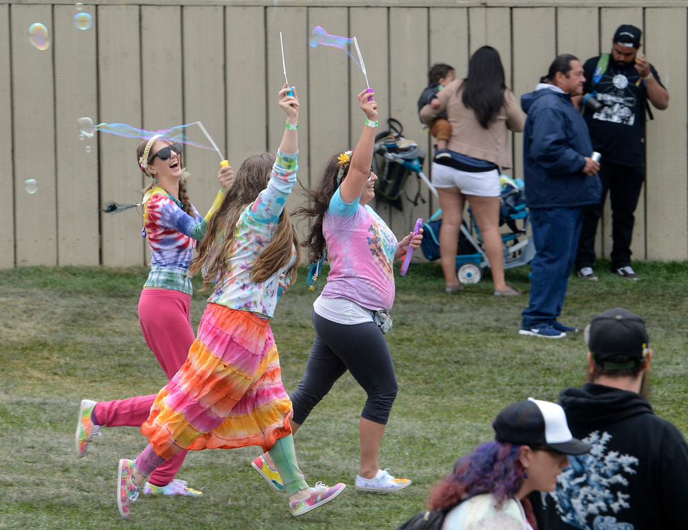 . Carly Lee, left, Karine Young and Cierra McBroom blow bubbles as RDGLDGRN perform at the California Roots Music and Art Festival at the Monterey County Fair and Events Center on Sunday May 28, 2017.  (David Royal - Monterey Herald)