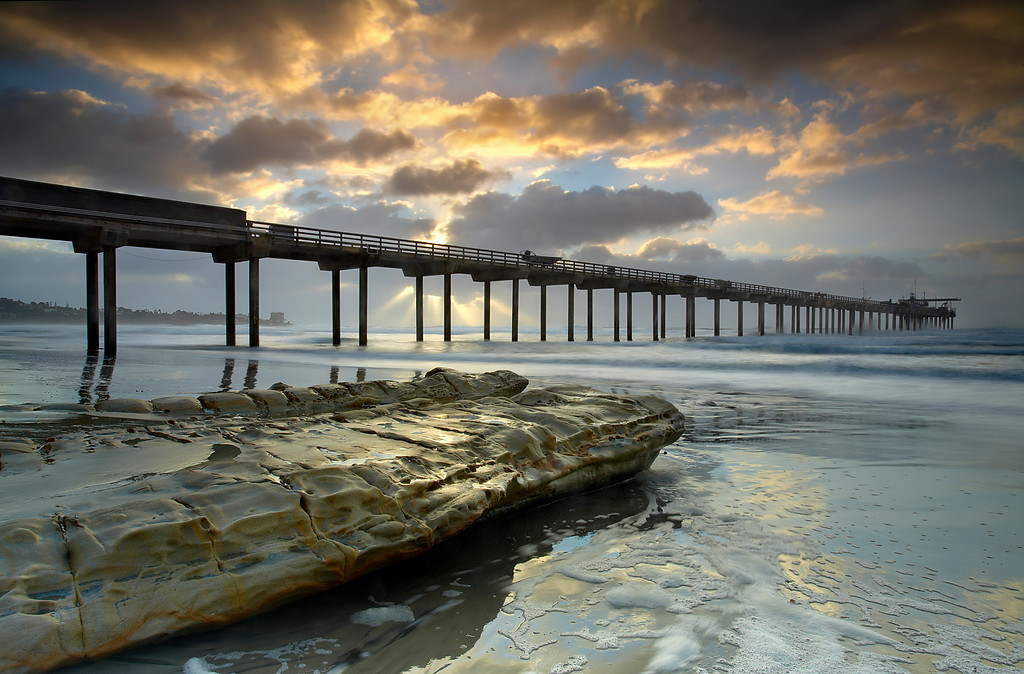 The Scripps Pier in La Jolla, California is used by oceanographers to do studies on the ocean and its effects on the rest of the planet. Before making this image, I waited for the light rays to arrange themselves between the pilings.  I also waited for the waves to pull back leaving foam on the sand.   I didn't have to wait too long because the wind was howling and the clouds were moving quickly.  The sea spray and rain made the shafts of light easily visible.  The rain also added depth to the image by having the background disappear into the mist.  I liked how the light brought out the colors in the foam on the sand.  Good atmosphere often produces subtle effects that you don't see on a clear day.