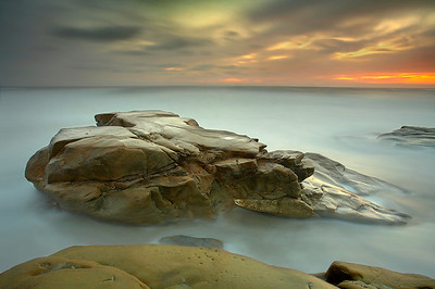 The sea can create some truly amazing structures.  Here in the sandstone, a giant heart-like formation has been worked into the stone by the relentless action of the pounding waves.  This is a very wide-angle shot of the sandstone heart taken from just about 15 feet away at a wide angle (17mm) just after sunset.   I used a long exposure to smooth the water around the heart and brighten the image a bit.  Only at high tide is the heart shape evident.