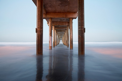 At sunrise, the first rays of light around the Scripps Pier had just touched the ocean creating this unusual effect that was enhanced by a long exposure time.  The waves were large, so I had to wait for a pullback in the water in order to show the glossy nature of the still wet sand.  Timing is everything, even on a 30 second exposure.  This is not a symmetrical and straight pier, so I made sure that I was centered in between the average lines made by the pilings and let the asymmetric elements stand out as they are.  The lights on the pier can still be seen in the water and the sunlight had just come into balance with the pier lights.