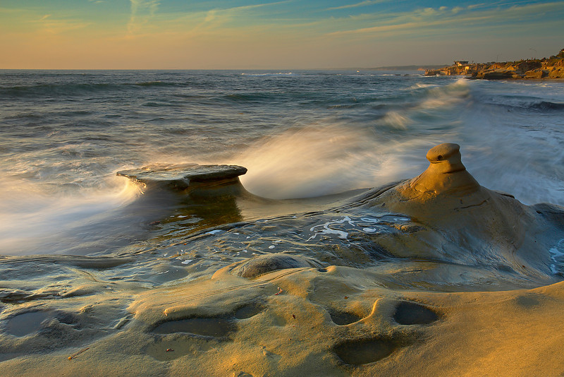 Large breakers washed over this 15-foot tall cliff on the edge of La Jolla's north shore near The Cove. I waited for the right wave in order to show the forces at work that carved the unusual rock formations in the area. Only during high tide at sunset is this possible because this area is dry at low tide.  A low warm light allowed just enough contrast and exposure time to show the water eroding the sandstone.