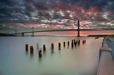 I have been to this spot many times hoping for a good sunrise and finally it happened.  I used the tower of the bridge to block the bright sun from creating lens flare.  Also, a medium tide is best for isolating the old pier pilings.  High tide nearly covers them and low tide make them too big to easily include in a decent composition.  This was about 1 minute before the lights were turned off.  The tripod was placed right on one of the square concrete posts with the legs shortened in order to be as close to the edge as possible.  I made sure to include the walkway for perspective and the feeling of actually being there for this amazing sunrise!