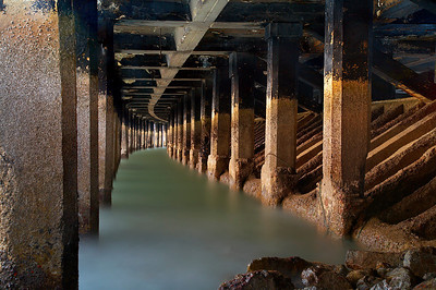 Another view of the curved pier at Aquatic Park at the end of Van Ness Avenue in San Francisco. The diagonal concrete pilings help to break the waves during high tides.  A low tide at sunset was required to get the shot looking right.  The extra long exposure gave this a smooth look.  A few big waves almost put my camera underwater but I held the tripod steady and took the hit in order to save the shot.  You only get one chance per night where the light is even enough to do this.  And I would have to wait a month for these conditions to happen again!