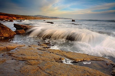 This beach just south of Pigeon Point is full of interesting rock formations. These rocks have been carved by waves like the one shown here. I watched the beach for 20 minutes, looking for interesting wave patterns and this was the best of them. So I set up the camera and tripod and waited for just the right moment.  I like how quiet the water is in the pool just before it is to be hit by the wave.