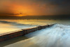 A thick fog began to clear as the sun rose, allowing the warm light to filter through to the sand. This groyne keeps the sand in place and has some good rich tones in the grain. The boats anchored offshore are there year round.