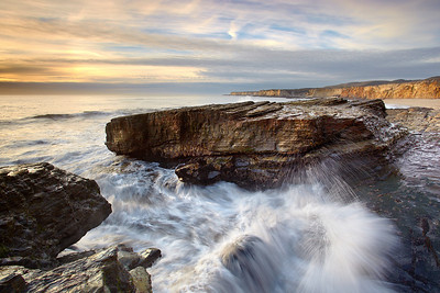 This is one of many rocky outcrops along this stretch of beach just north of Santa Cruz, California.  I often wonder how long this rock has been pounded by long-forgotton storms over the millenia.  I waited for the light to strike the cliffs and for a nice wave (not too big or small) to strike the rock.
