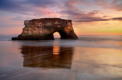 Natural Bridges State Park in Santa Cruz is a great place to watch the sunset. This is one of the few remaining arches, as the  other ones have been washed into the sea. New ones will replace them as the years go by. The tip of the Monterey Peninsula and  the start of the Big Sur coast 40 miles away are shown in the middle of the arch.   In order to show this arch in the best light, I had to wait until November for the setting sun to be at the best angle to show the  detail on the arch face.  I also wanted some cloud cover, which becomes more common as the 7 month summer dry season comes  to a close at this time of year.  I used a long exposure to smooth the water, highlighting the arch and distant coastline.  And I  timed it for when the sand was at its most reflective state at low tide.