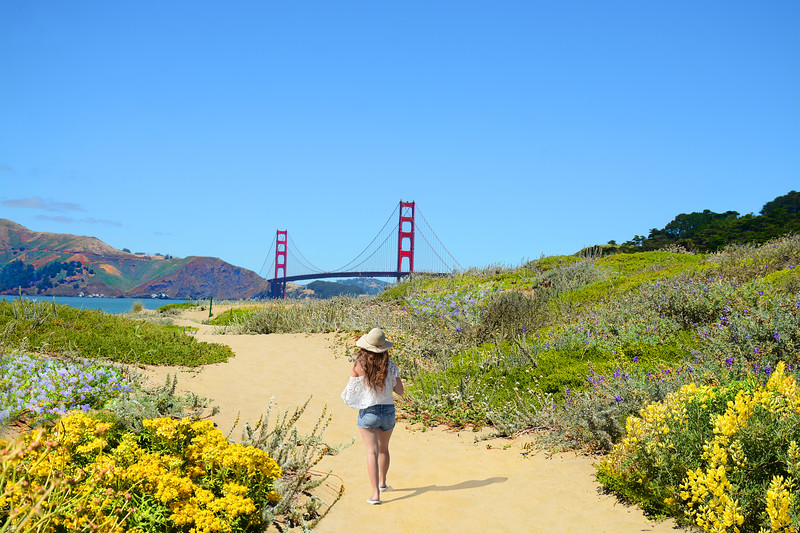 Woman on hiking trip,girl walking on pathway enjoying beautiful coastal landscape. Golden Gate Bridge, over Pacific Ocean and San Francisco Bay, Baker Beach, San Francisco, California, USA