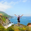 Man  standing on the top of the mountain with her  hands up looking at beautiful coastal ocean mountain landscape during  hiking trip.  Pacific Ocean.Big Sur, California, USA