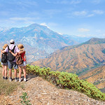 Father with arms around his family  looking at beautiful summer mountains landscape, on hiking trip .Kings Canyon National Park, southern Sierra Nevada, east of Fresno, California. ,USA.