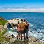 Father with arms around his family looking at beautiful ocean view. People on hiking trip in the mountains. Santa Cruz, California, USA