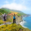 People with hands up looking at beautiful summer mountains landscape.Couple on hiking trip, Bixby Bridge,  famous bridge on highway 1 in California over Pacific Ocean. Big Sur, California, USA