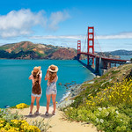 Friends enjoying time together on vacation  trip.  Girls looking at beautiful view of Golden Gate Bridge, over Pacific Ocean. San Francisco, California, USA