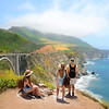 Family looking at beautiful summer mountains landscape, on hiking trip   Bixby Bridge,  famous bridge on highway 1 in California over Pacific Ocean. Big Sur, California, USA