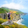 Man  standing on the top of the mountain with her  hands up looking at beautiful coastal ocean mountain landscape during  hiking trip. Bixby Bridge, Pacific Ocean.Big Sur, California, USA