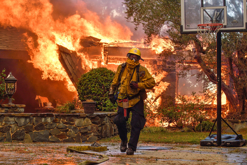 . Firefighters work to extinguish a fire at a home as they battle a wildfire in Anaheim Hills, Calif., Monday, Oct. 9, 2017. Wildfires whipped by powerful winds swept through Northern California sending residents on a headlong flight to safety through smoke and flames as homes burned. (Jeff Gritchen/The Orange County Register via AP)