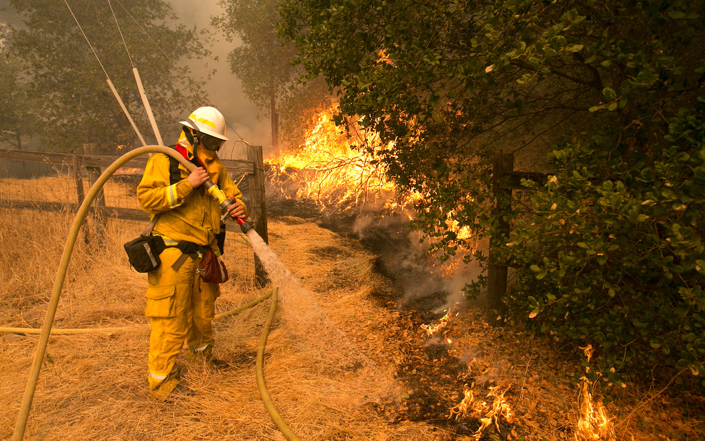 . Napa County firefighter James George hoses down a fire line approaching a home Monday, Oct. 9, 2017, in Napa, Calif. Wildfires whipped by powerful winds swept through Northern California sending resident on a headlong flight to safety through smoke and flames as homes burned. (AP Photo/Rich Pedroncelli)