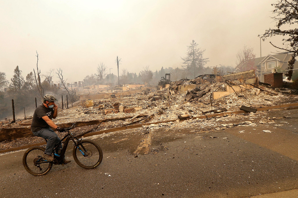 . A man rides a bicycle past burned down homes in Santa Rosa, Calif., Monday, Oct. 9, 2017. Wildfires whipped by powerful winds swept through Northern California early Monday, sending residents on a headlong flight to safety through smoke and flames as homes burned. (AP Photo/Jeff Chiu)