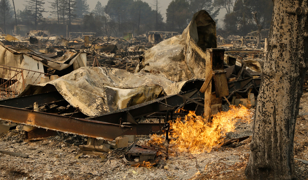 . Remains from a wildfire sit at the Journey\'s End mobile home park on Monday, Oct. 9, 2017, in Santa Rosa, Calif. Wildfires whipped by powerful winds swept through Northern California sending residents on a headlong flight to safety through smoke and flames as homes burned. (AP Photo/Ben Margot)