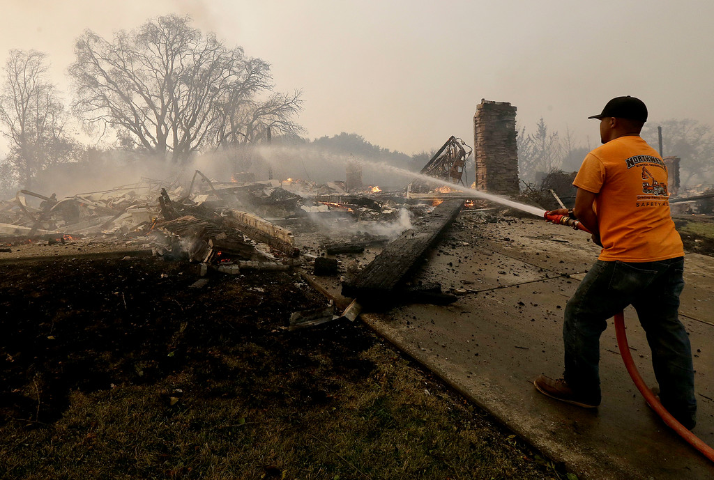 . A man hoses down hot spots where a house burned down in Santa Rosa, Calif., Monday, Oct. 9, 2017. Wildfires whipped by powerful winds swept through Northern California, sending residents on a headlong flight to safety through smoke and flames as homes burned. (AP Photo/Jeff Chiu)
