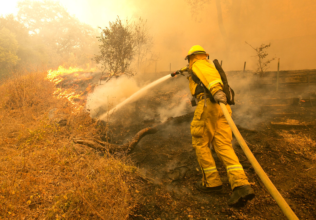 . Napa County firefighter James George hoses down a fireline approaching a home Monday, Oct. 9, 2017, in Napa, Calif. Wildfires whipped by powerful winds swept through Northern California early Monday, sending residents on a headlong flight to safety through smoke and flames as homes burned. (AP Photo/Rich Pedroncelli)
