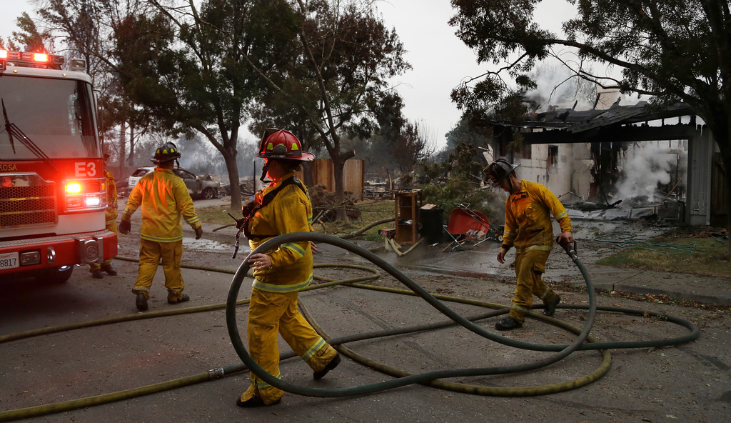 . Santa Rosa firefighters carry hose as they battle hotspots in the Coffey Park area of Santa Rosa, Calif., on Tuesday, Oct. 10, 2017. An onslaught of wildfires across a wide swath of Northern California broke out almost simultaneously then grew exponentially, swallowing up properties from wineries to trailer parks and tearing through both tiny rural towns and urban subdivisions. (AP Photo/Ben Margot)