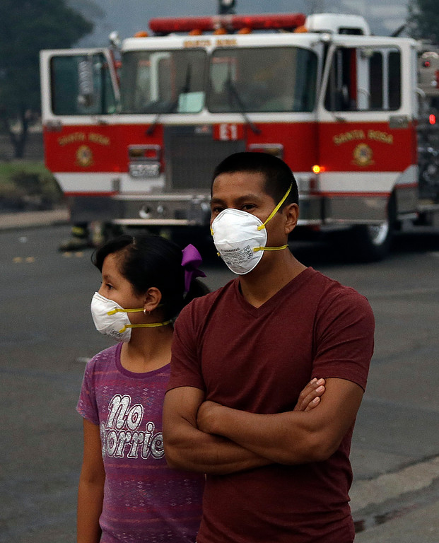 . Pedestrians wear masks as they watch firemen battle a fire in a business on Monday, Oct. 9, 2017, in Santa Rosa, Calif. Wildfires whipped by powerful winds swept through Northern California early Monday, sending residents on a headlong flight to safety through smoke and flames as homes burned. (AP Photo/Ben Margot)