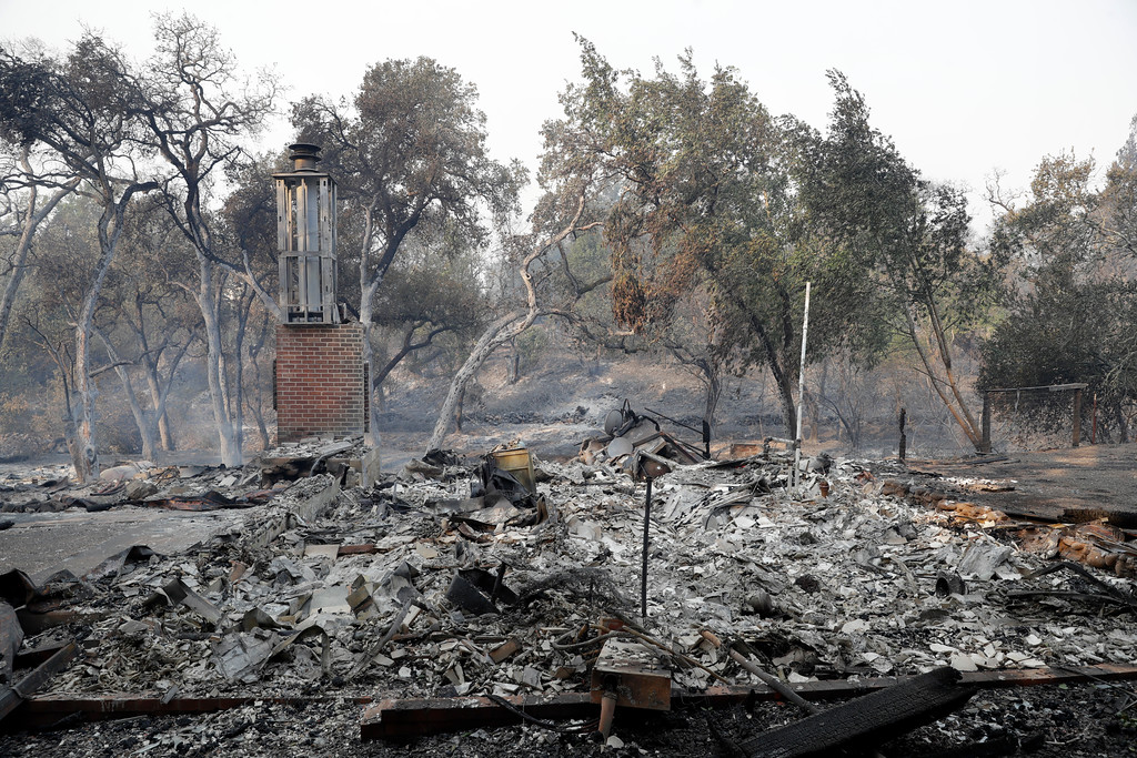 . A chimney still stands at a fire-ravaged property along Soda Canyon Road, Monday, Oct. 9, 2017, in Napa, Calif. Wildfires whipped by powerful winds swept through Northern California sending residents on a headlong flight to safety through smoke and flames as homes burned. (AP Photo/Marcio Jose Sanchez)