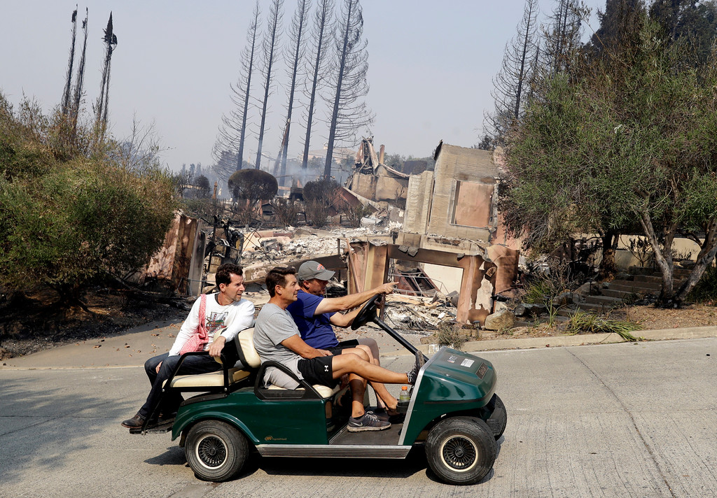 . People drive by in a a golf cart in front of a fire-ravaged property in the Silverado Crest subdivision Monday, Oct. 9, 2017, in Napa, Calif. Wildfires whipped by powerful winds swept through Northern California sending residents on a headlong flight to safety through smoke and flames as homes burned. (AP Photo/Marcio Jose Sanchez)