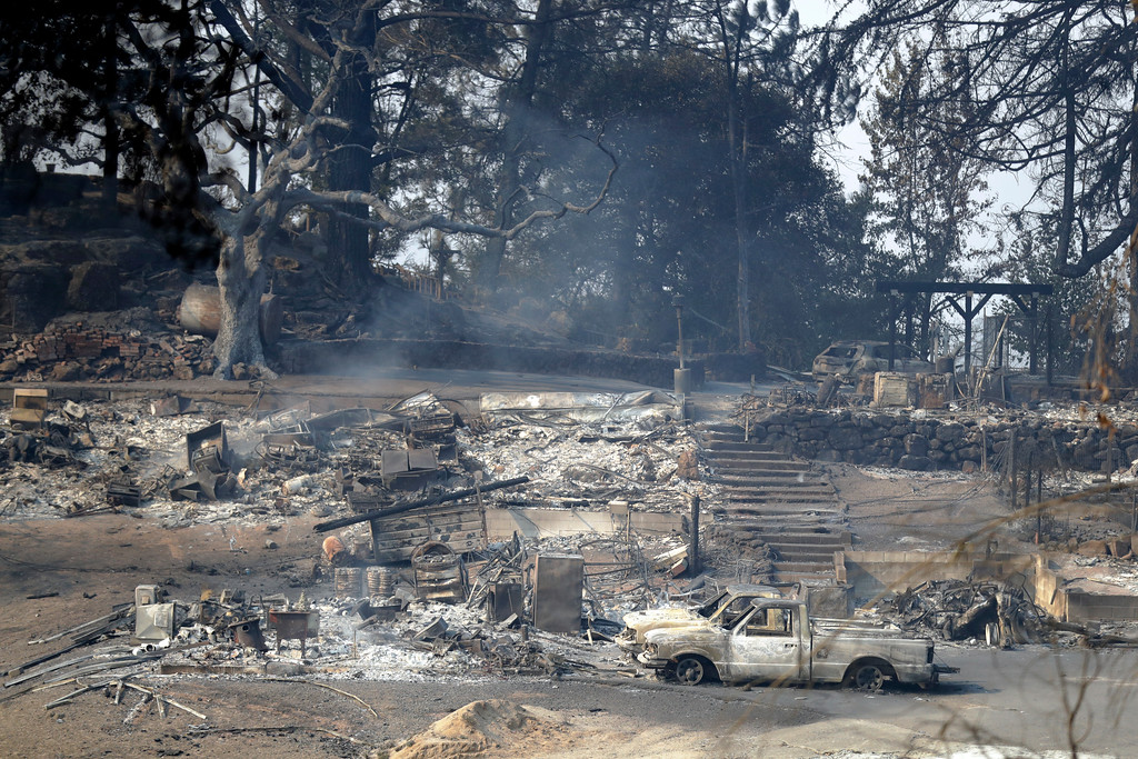 . A fire-ravaged property is seen along Atlas Peak Road, Monday, Oct. 9, 2017, in Napa, Calif. Wildfires whipped by powerful winds swept through Northern California sending residents on a headlong flight to safety through smoke and flames as homes burned. (AP Photo/Marcio Jose Sanchez)