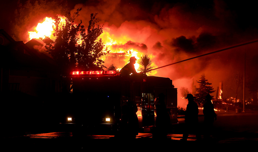 . Gold Fidge firefighters use a deck gun to protect structures in Coffey Park in Santa Rosa, Calif., Monday Oct. 9, 2017. More than a dozen wildfires whipped by powerful winds been burning though California wine country. The flames have destroyed at least 1,500 homes and businesses and sent thousands of people fleeing. (Kent Porter/The Press Democrat via AP)