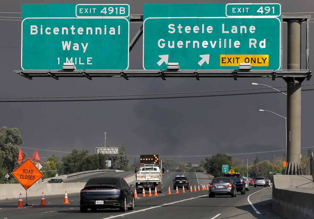 . Traffic is diverted off northbound highway 101 at Steele Lane on Monday, Oct. 9, 2017, in Santa Rosa, Calif. Wildfires whipped by powerful winds swept through Northern California, sending residents on a headlong flight to safety through smoke and flames as homes burned. (AP Photo/Ben Margot)