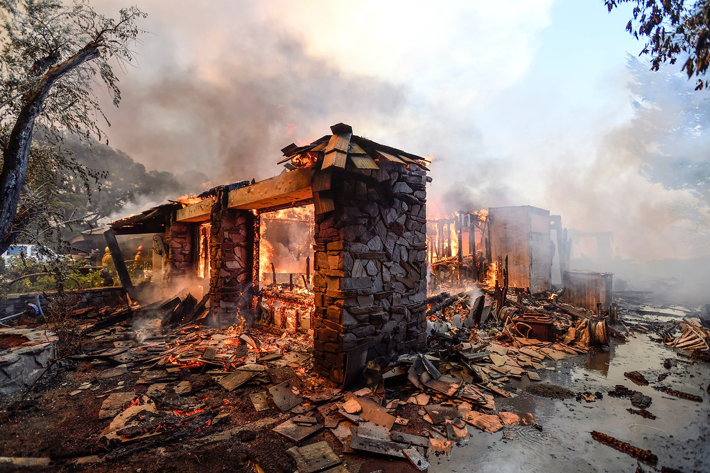 . Flames from a wildfire burn a home in Anaheim Hills, Calif., Monday, Oct. 9, 2017. Wildfires whipped by powerful winds swept through Northern California sending residents on a headlong flight to safety through smoke and flames as homes burned. (Jeff Gritchen/The Orange County Register via AP)