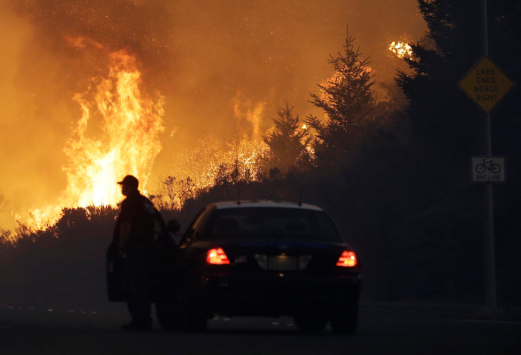 . A law enforcement officer blocks a road as flames burn in a residential area in Santa Rosa, Calif., Monday, Oct. 9, 2017. Wildfires whipped by powerful winds swept through Northern California early Monday, sending residents on a headlong flight to safety through smoke and flames as homes burned. (AP Photo/Jeff Chiu)