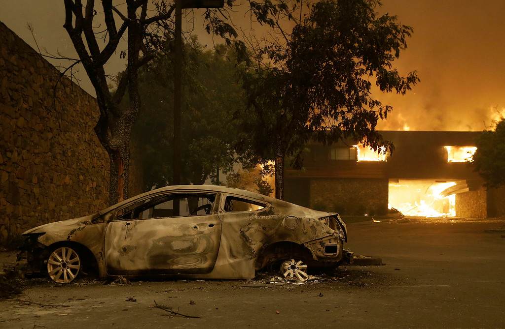 . The remains of a car sits near the Fountaingrove Inn Hotel as it burns at rear in Santa Rosa, Calif., Monday, Oct. 9, 2017. (AP Photo/Jeff Chiu)