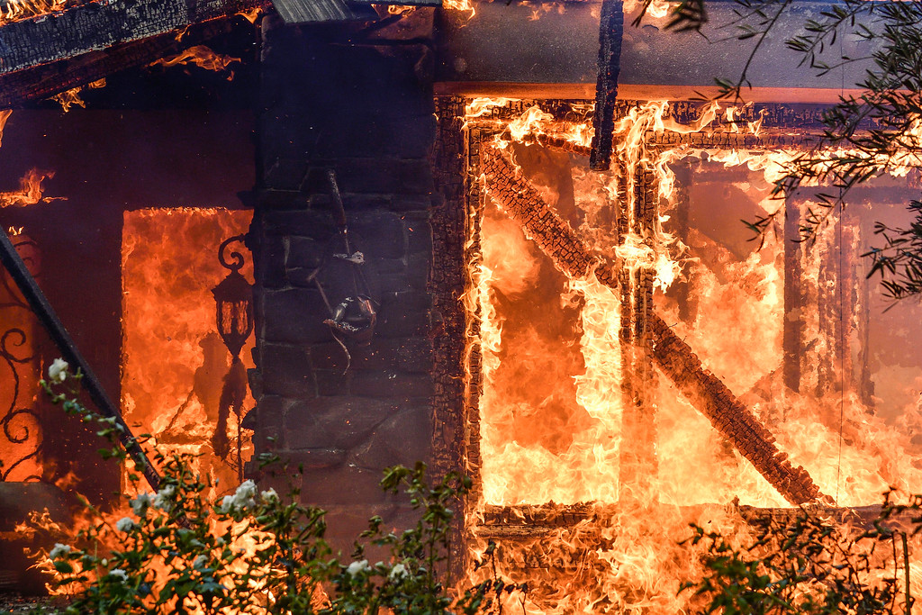 . Flames from a wildfire consume a home in Anaheim Hills, Calif., Monday, Oct. 9, 2017. Wildfires whipped by powerful winds swept through Northern California sending residents on a headlong flight to safety through smoke and flames as homes burned. (Jeff Gritchen/The Orange County Register via AP)