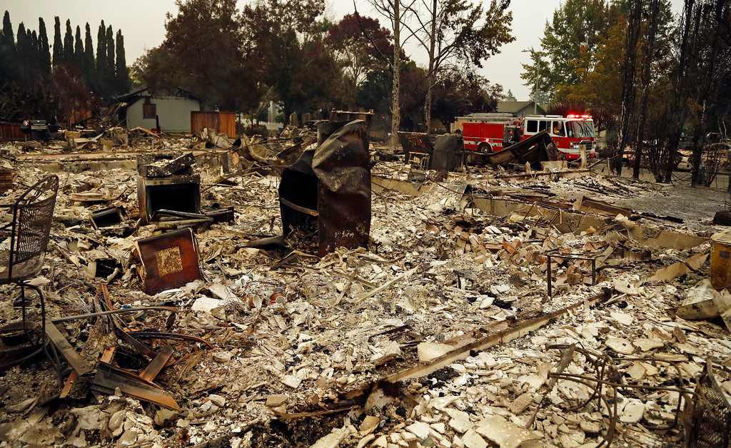 . Firefighters drive through the Coffey Park area of Santa Rosa, Calif., looking for hotspots on Tuesday, Oct. 10, 2017. An onslaught of wildfires across a wide swath of Northern California broke out almost simultaneously then grew exponentially, swallowing up properties from wineries to trailer parks and tearing through both tiny rural towns and urban subdivisions. (AP Photo/Ben Margot)