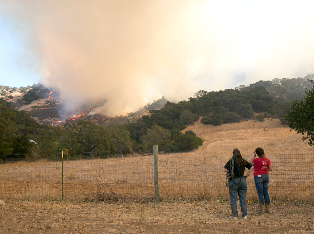 . Area residents watch as flames from a massive wildfire burn in the hills Monday, Oct. 9, 2017, in Napa, Calif. Wildfires whipped by powerful winds swept through Northern California sending resident on a headlong flight to safety through smoke and flames as homes burned. (AP Photo/Rich Pedroncelli)