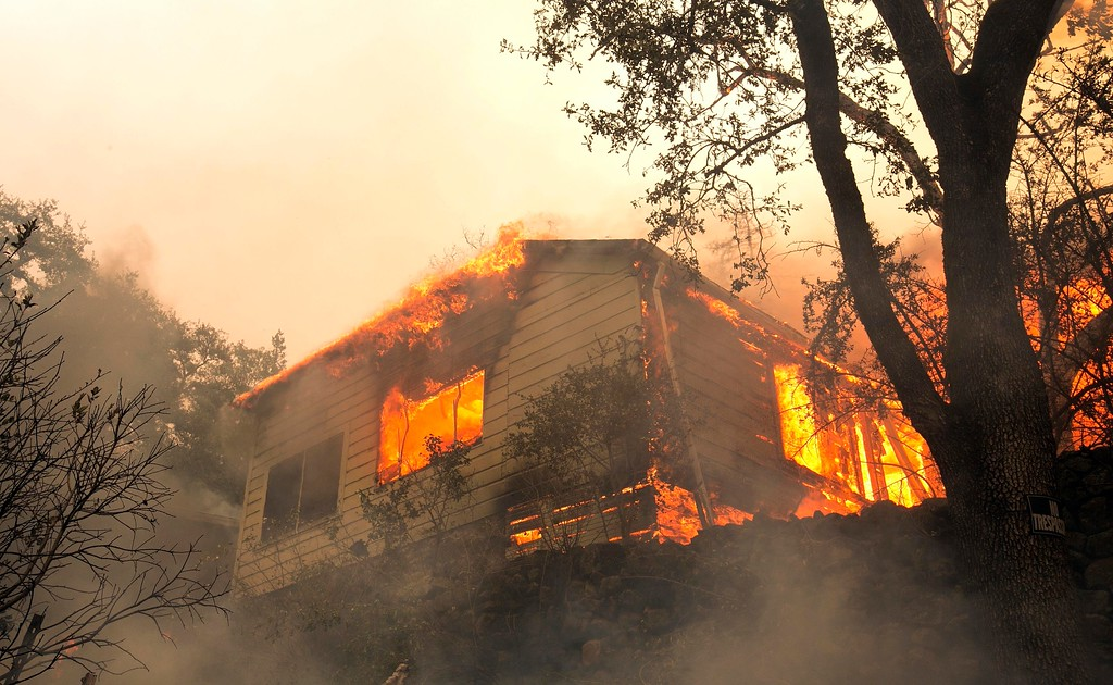 . Flames from a massive wildfire consume a home on the Silverado Trail, Monday, Oct. 9, 2017, east of Napa, Calif. (AP Photo/Rich Pedroncelli)