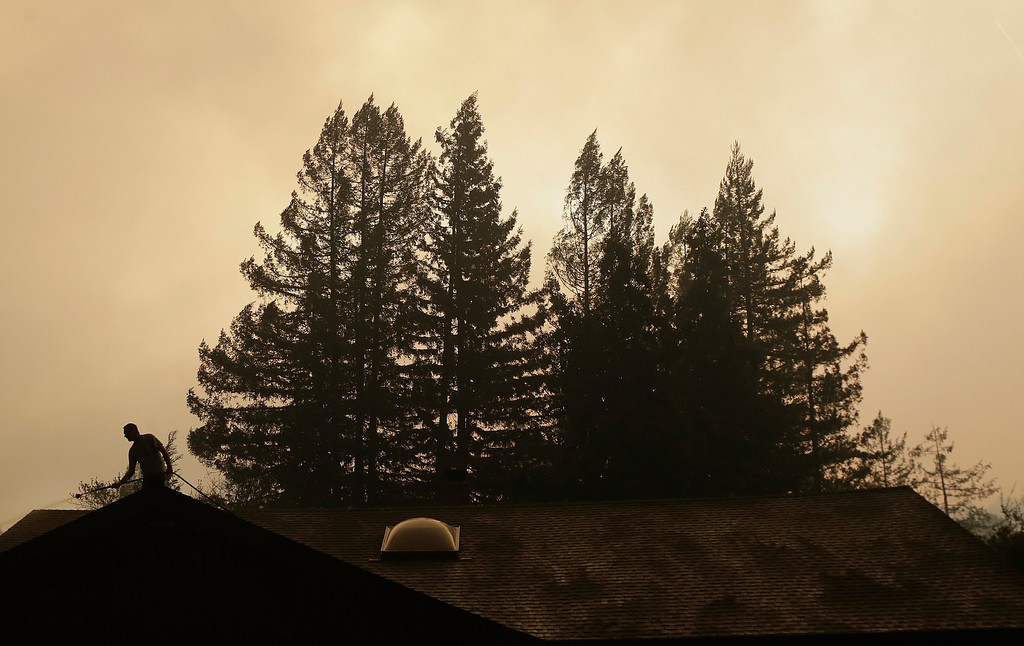 . A man hoses the roof of a home in Santa Rosa, Calif., Monday, Oct. 9, 2017. Wildfires whipped by powerful winds swept through Northern California early Monday, sending residents on a headlong flight to safety through smoke and flames as homes burned. (AP Photo/Jeff Chiu)