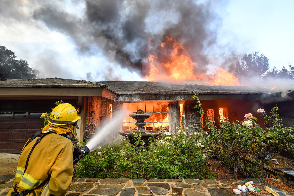 . Firefighters work to extinguish a fire as they battle a wildfire in Anaheim Hills, Calif., Monday, Oct. 9, 2017. Wildfires whipped by powerful winds swept through Northern California sending residents on a headlong flight to safety through smoke and flames as homes burned. (Jeff Gritchen/The Orange County Register via AP)