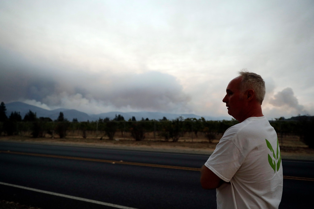 . Curtis Capitani walks along Trancas street in front of a plume of smoke from a wildfire Monday, Oct. 9, 2017, in Napa, Calif. (AP Photo/Marcio Jose Sanchez)