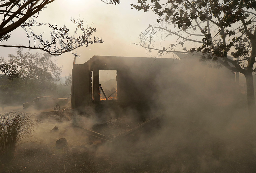 . Smoke blows past a burning house in Santa Rosa, Calif., Monday, Oct. 9, 2017. Wildfires whipped by powerful winds swept through Northern California, sending residents on a headlong flight to safety through smoke and flames as homes burned. (AP Photo/Jeff Chiu)