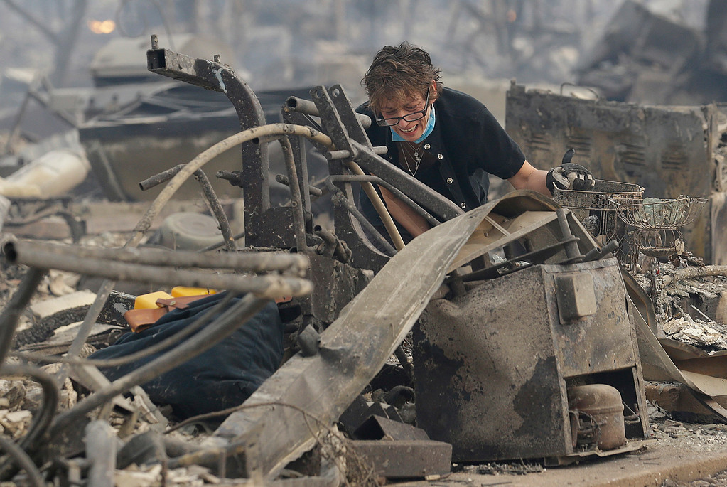 . Kristine Pond reacts as she searches the remains of her family\'s home destroyed by fires in Santa Rosa, Calif., Monday, Oct. 9, 2017. (AP Photo/Jeff Chiu)