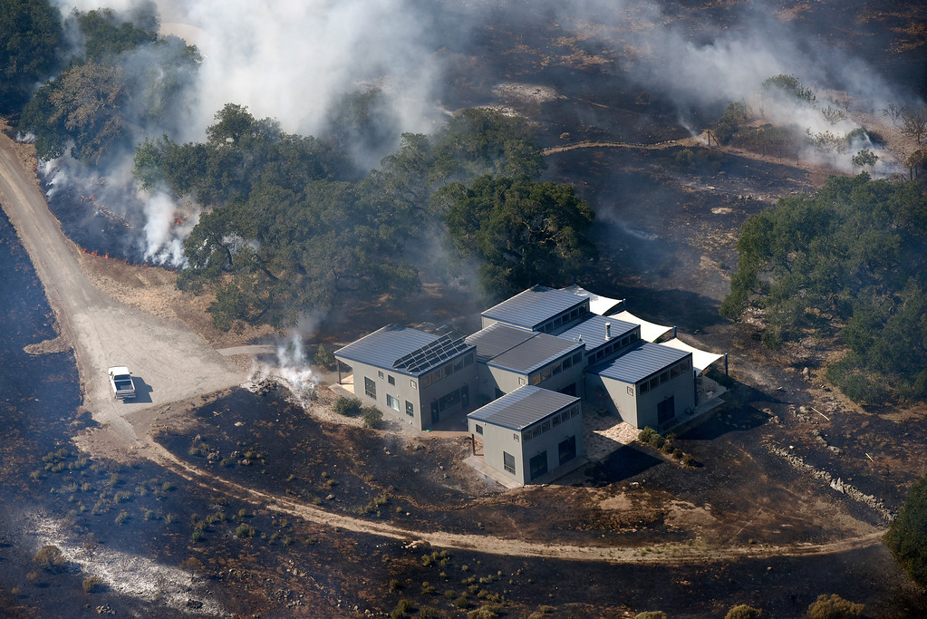 . Smoke rises as a wildfire burns near a structure in the hills east of downtown Napa, Calif., Monday, Oct. 9, 2017. Wildfires whipped by powerful winds swept through Northern California sending residents on a headlong flight to safety through smoke and flames as homes burned. (Michael Short/San Francisco Chronicle via AP)